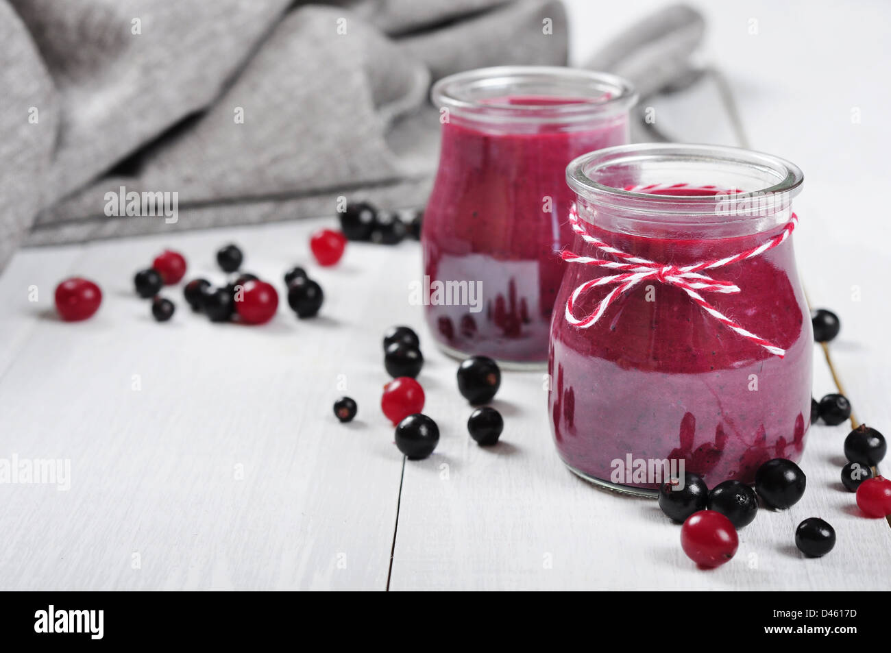 Cranberry and black currant smoothie in glass jars on a white wooden background Stock Photo