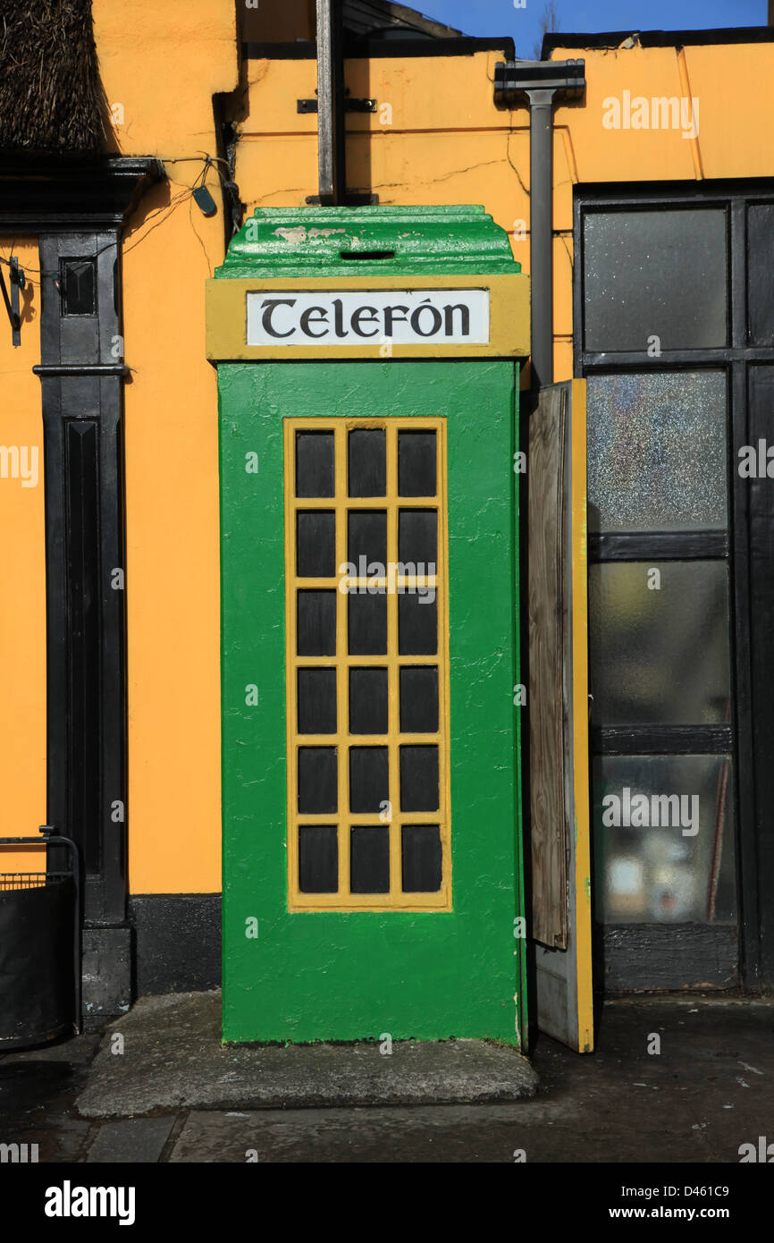old style telephone box painted in green and gold,  on an irish roadside, irish telephone kiosk common in the irish - Stock Image