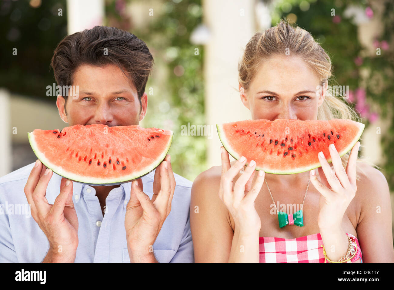 Mother And Daughter Enjoying Slices Of Water Melon - Stock Image