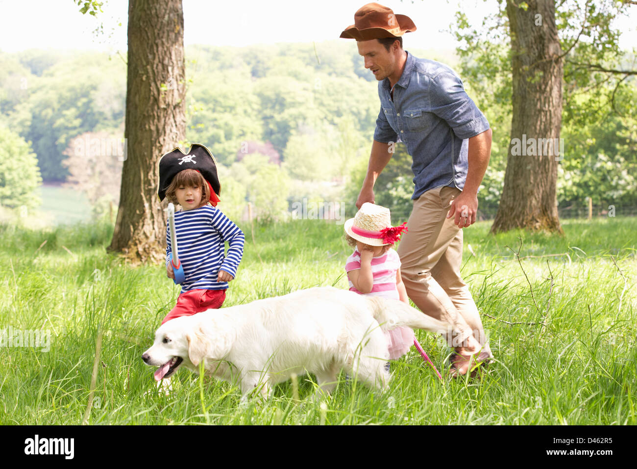 Father Playing Exciting Adventure Game With Children And Dog In Summer Field - Stock Image