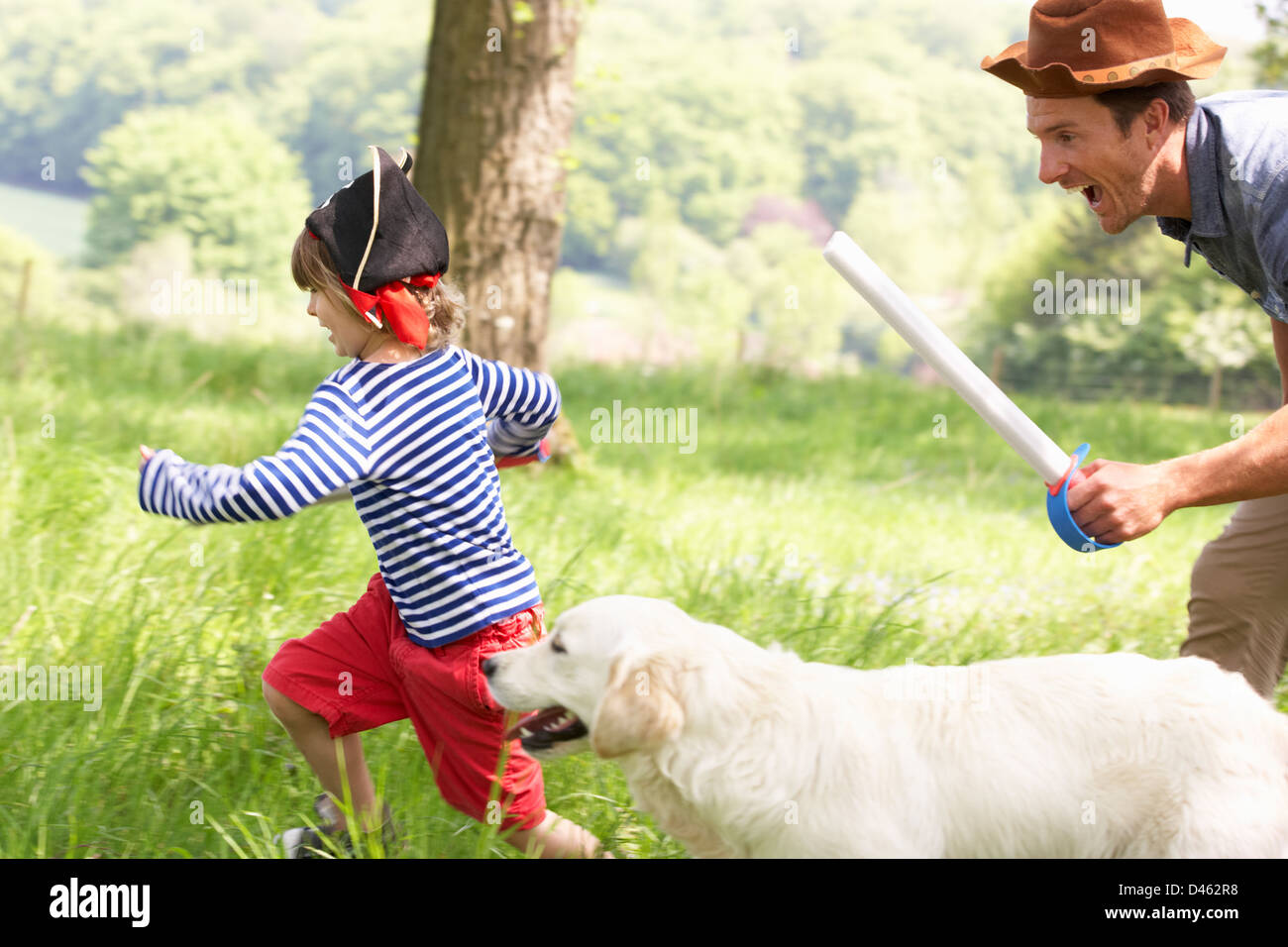 Father Playing Exciting Adventure Game With Son And Dog In Summer Field - Stock Image