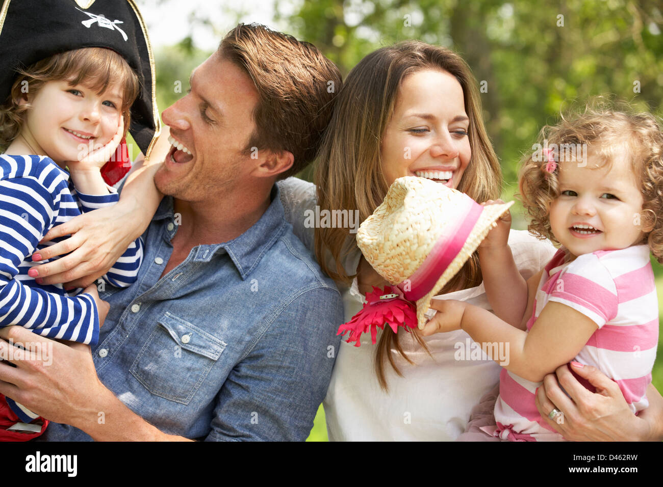 Parents Playing Exciting Adventure Game With Children In Summer Field - Stock Image