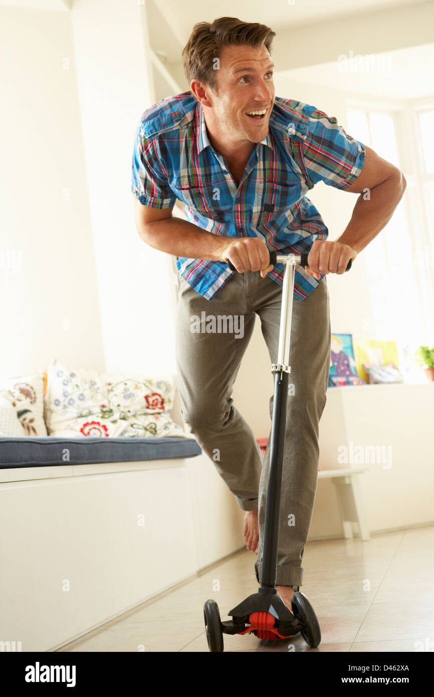 Man Riding Child's Scooter Indoors Stock Photo