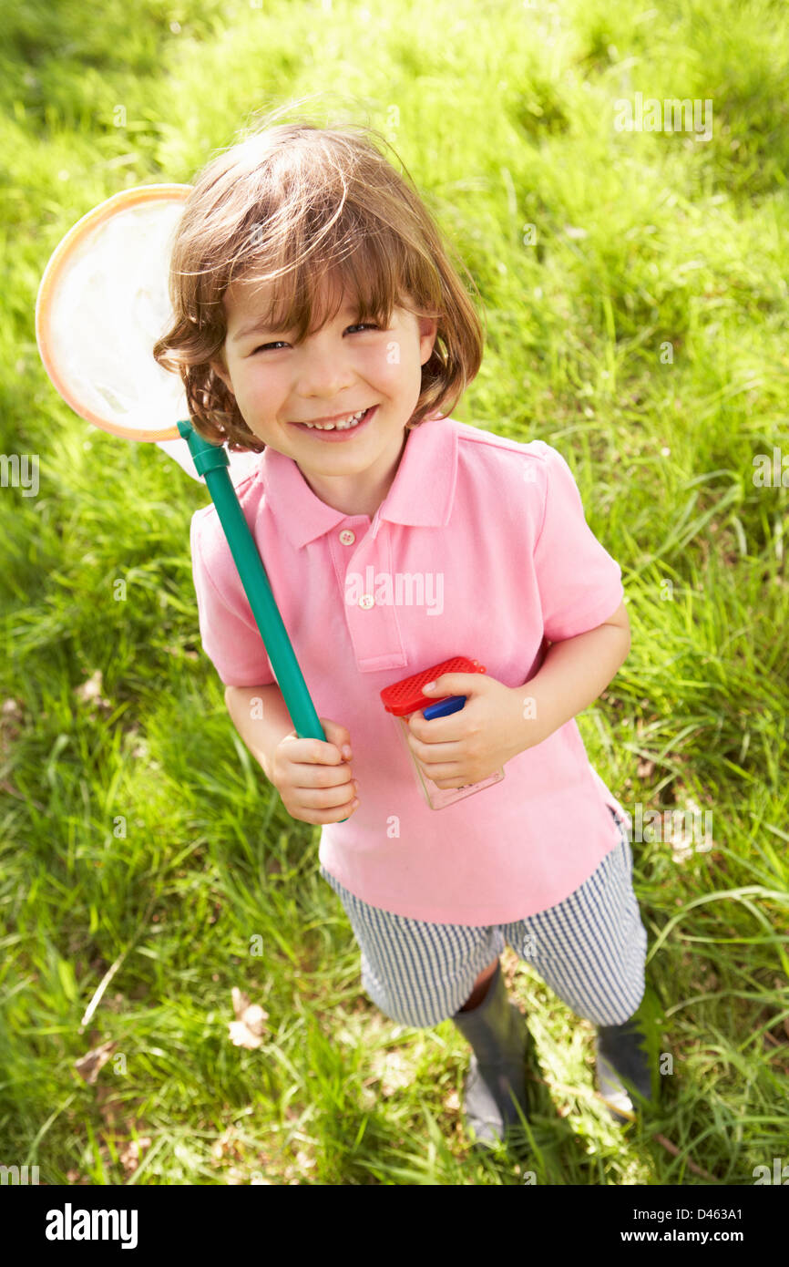 Young Boy In Field With Net And Bug Catcher - Stock Image