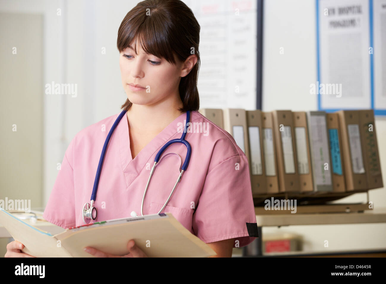 Nurse Reading Patient Notes At Nurses Station - Stock Image