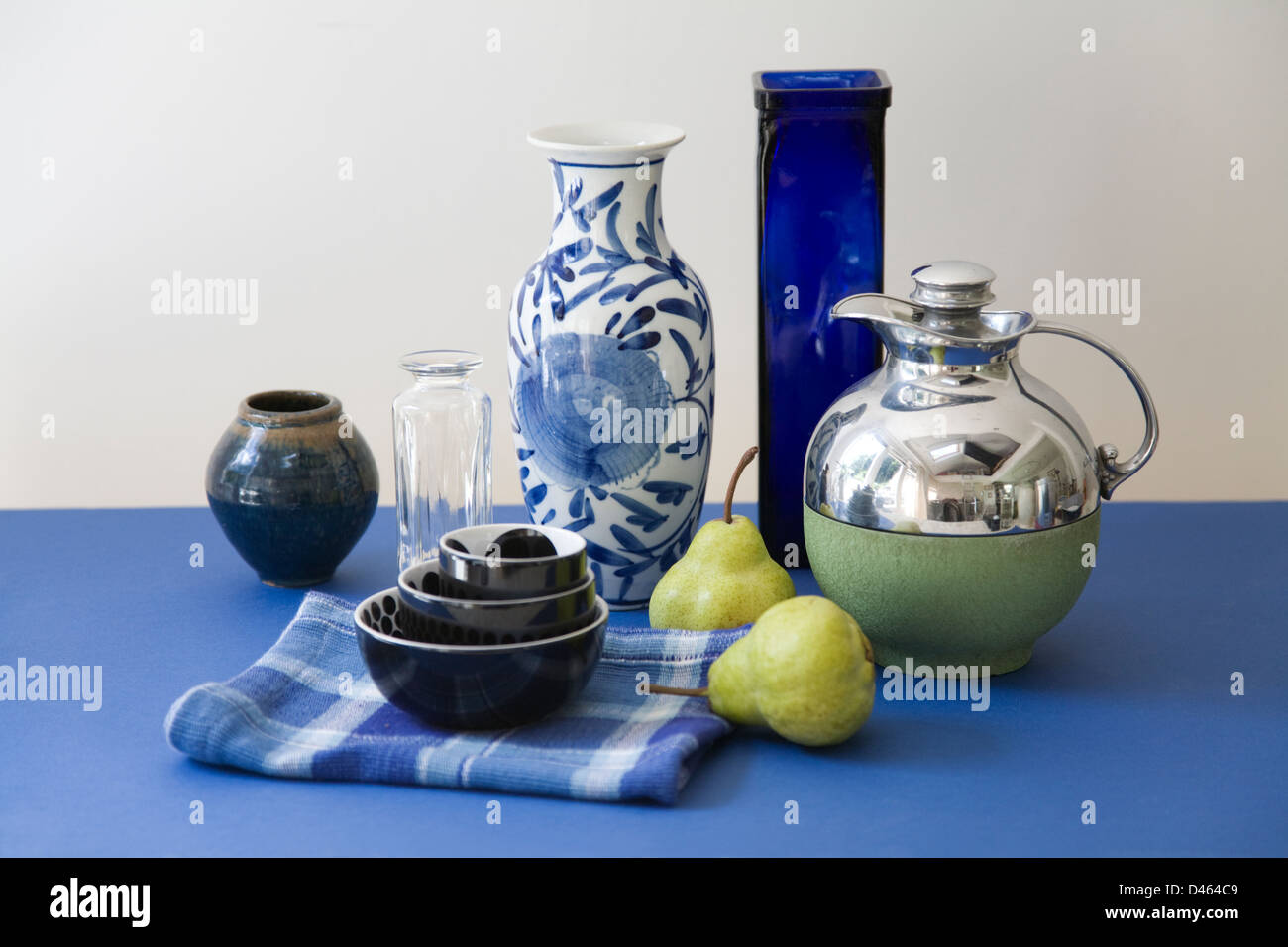 Colour co-ordinated still life of crockery and pears on a blue table with a neutral background - Stock Image