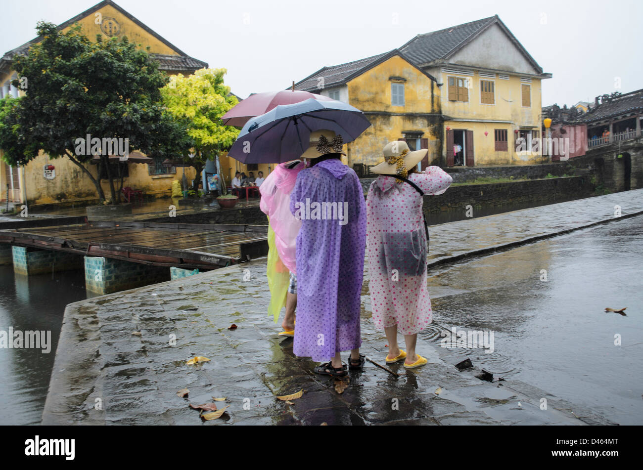 Tourists in rain gear on a rainy day in Hoi An Vietnam Stock Photo