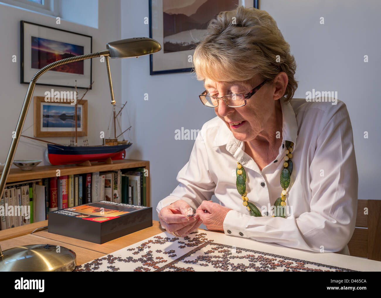 Elderly woman, OAP with jigsaw at home UK - Stock Image