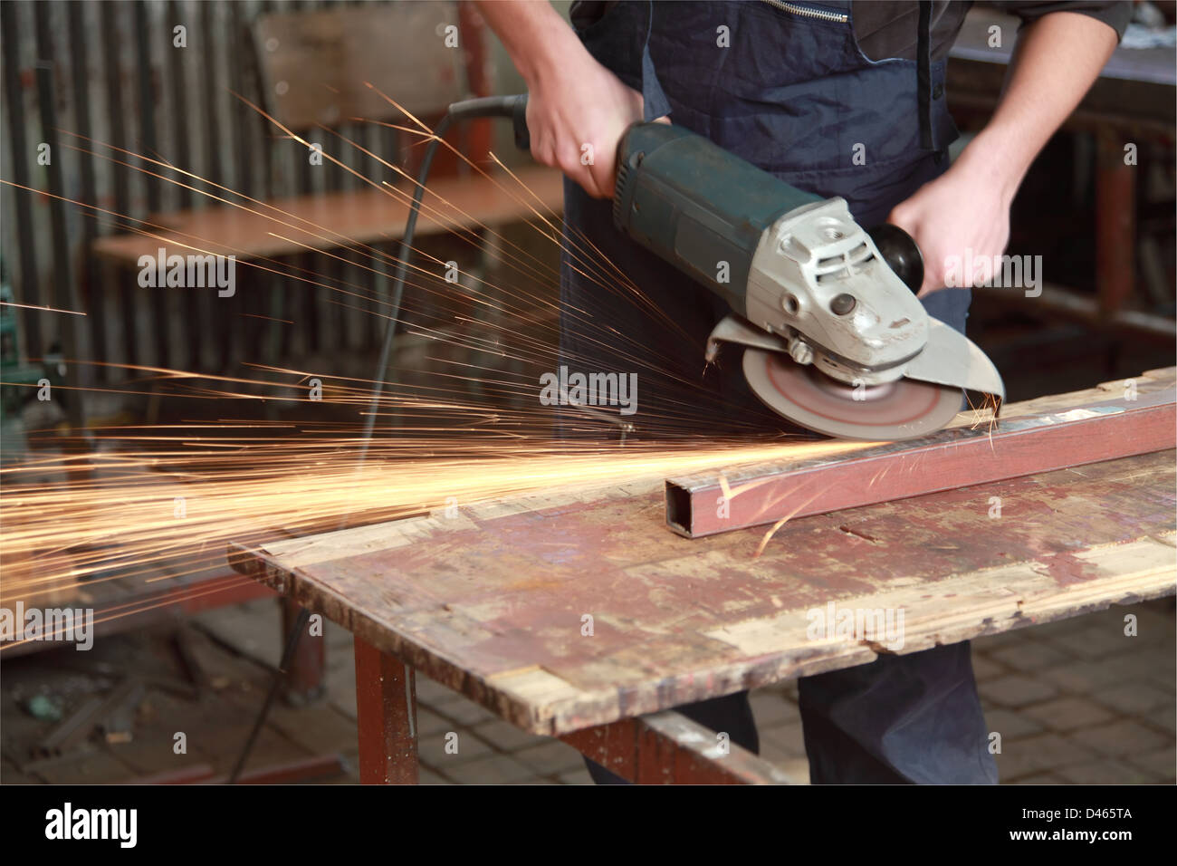Grinding, close up of workers hand, tool and sparks - Stock Image