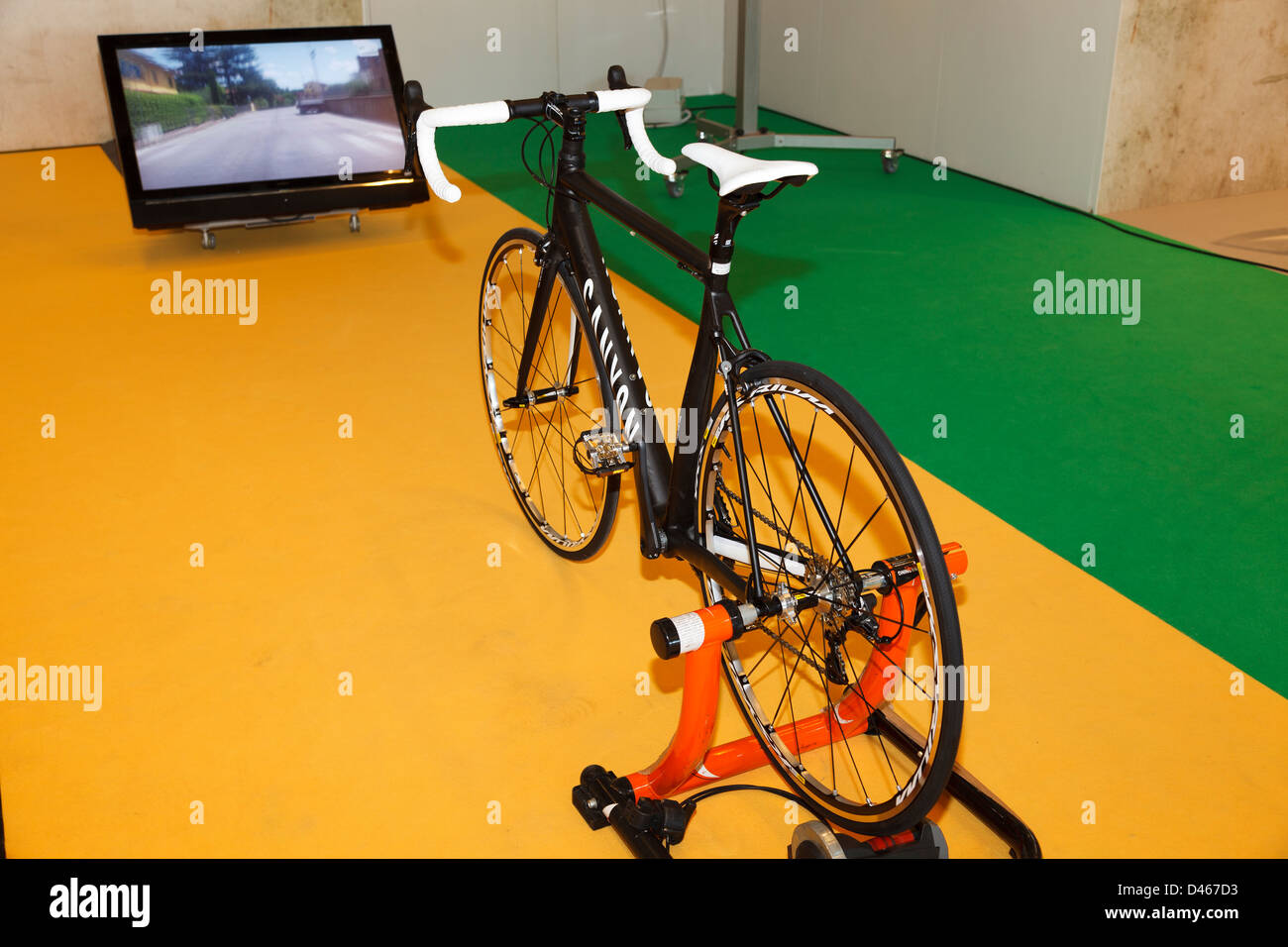 Racing bike connected to the TV by Canyon Factory - Stock Image