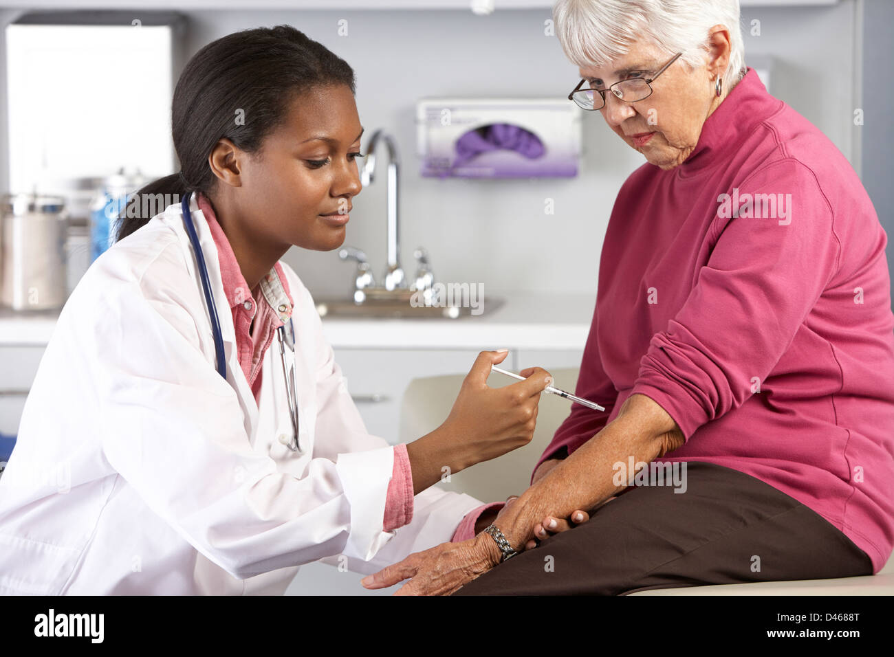 Doctor Giving Senior Female Patient Injection - Stock Image