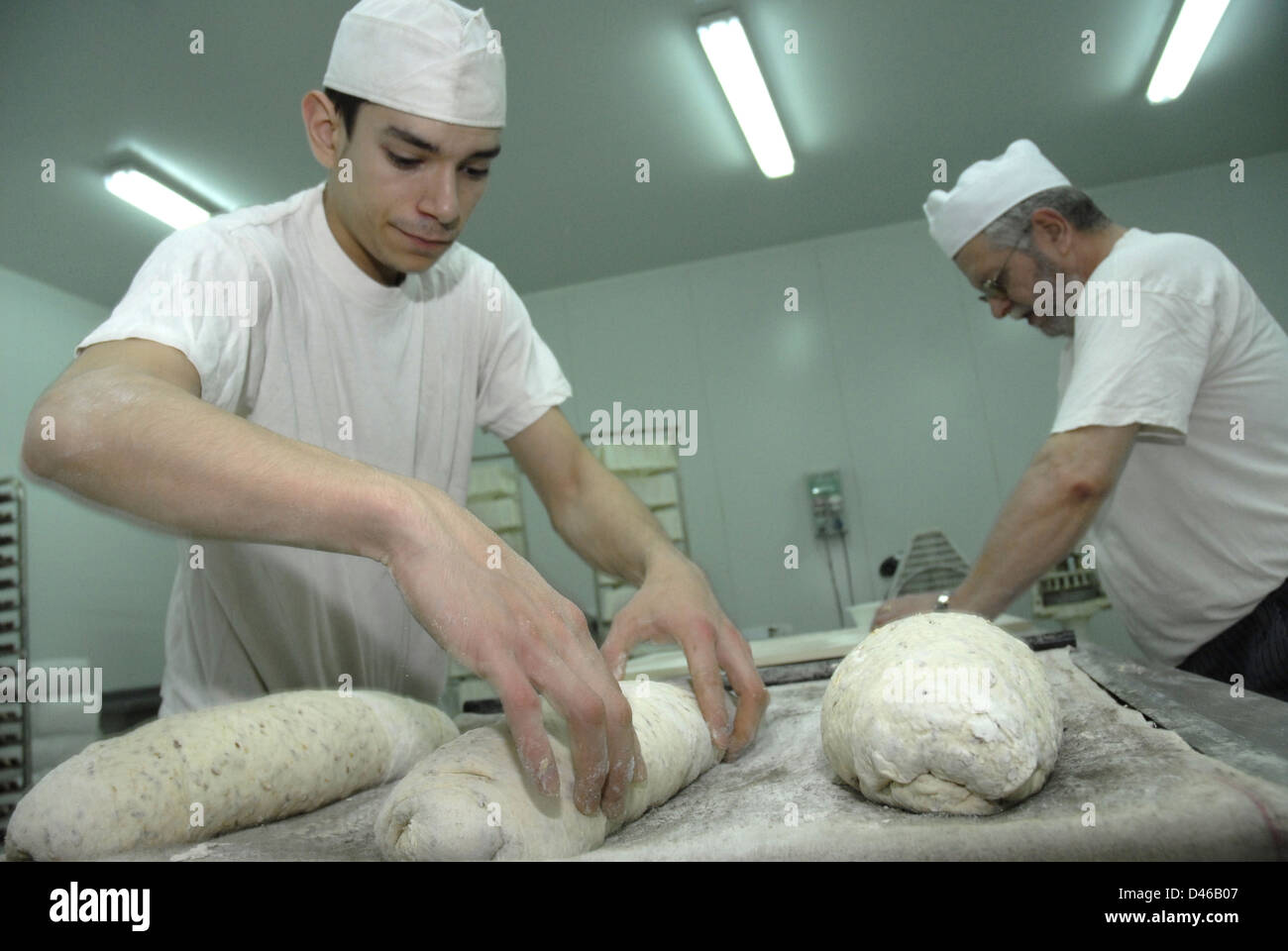 A worker of the bakery, elaboration of artisan bread in the bakery - Stock Image