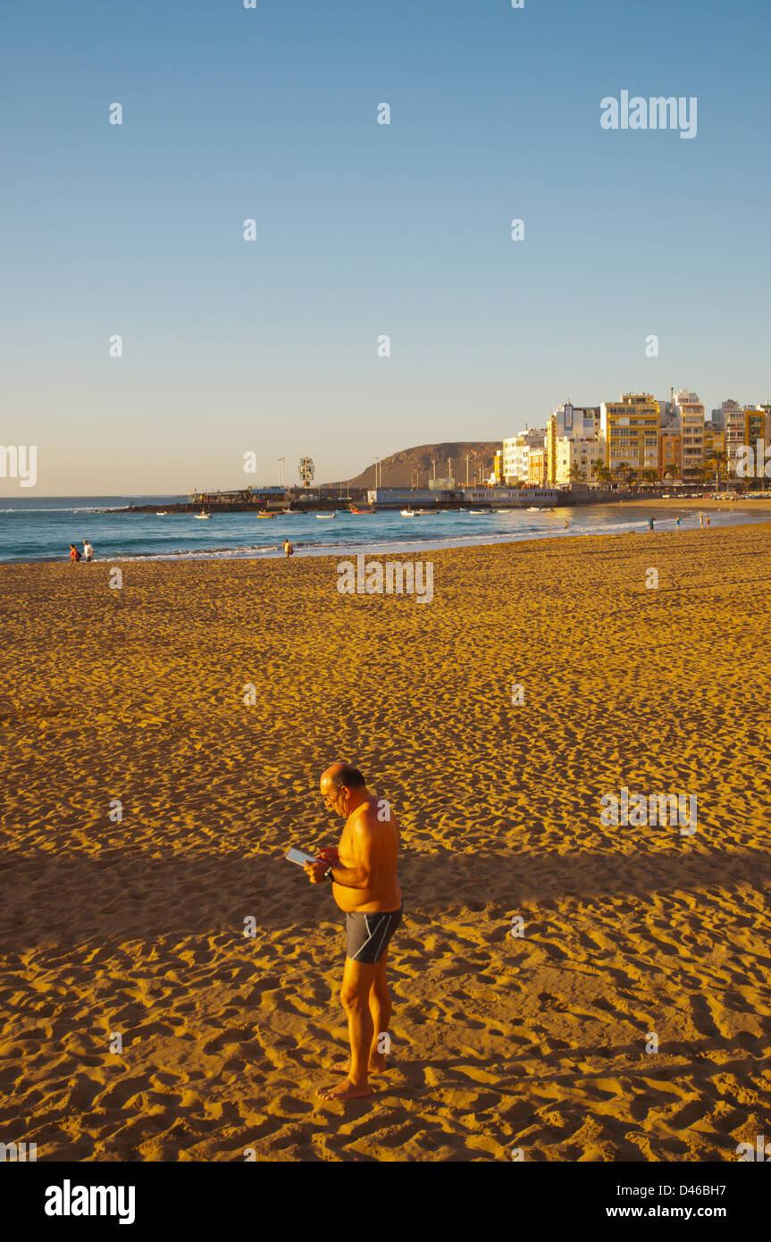 Man using tablet computer Playa de las Canteras beach Santa Catalina district Las Palmas de Gran Canaria island - Stock Image