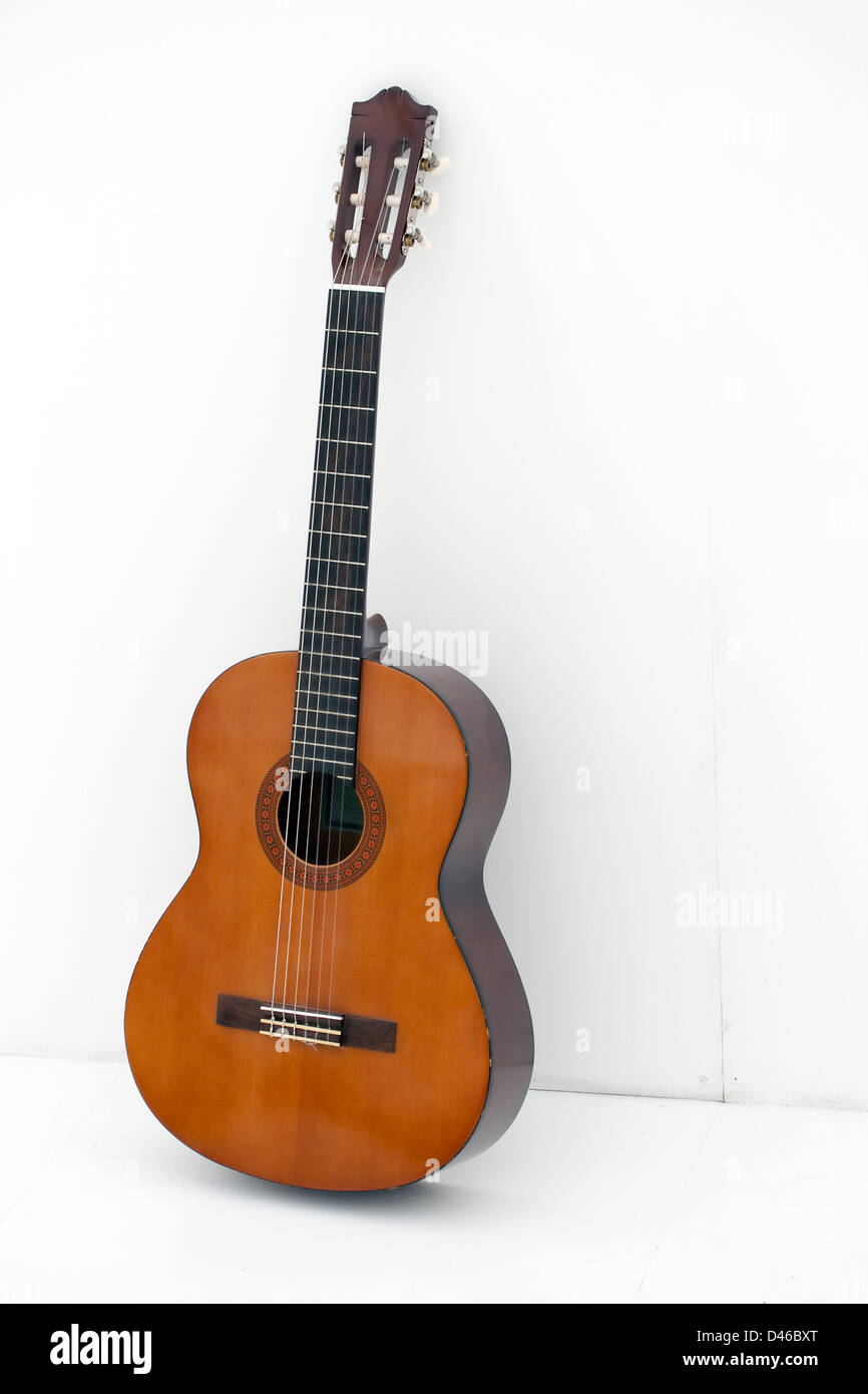 acoustic guitar leaning on a white wall - Stock Image