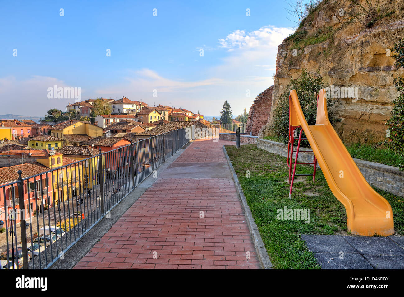 Yellow children slide on public playground in small town of Diano D'Alba in Piedmont, Northern Italy. - Stock Image