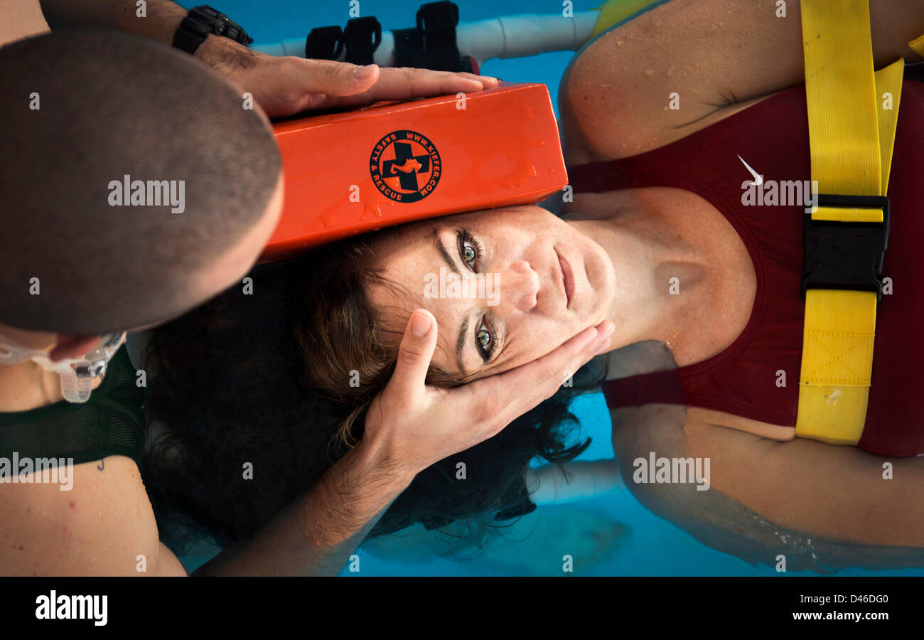 A US Marine instructor demonstrates the proper technique for treating head, neck and spinal injuries in the water - Stock Image