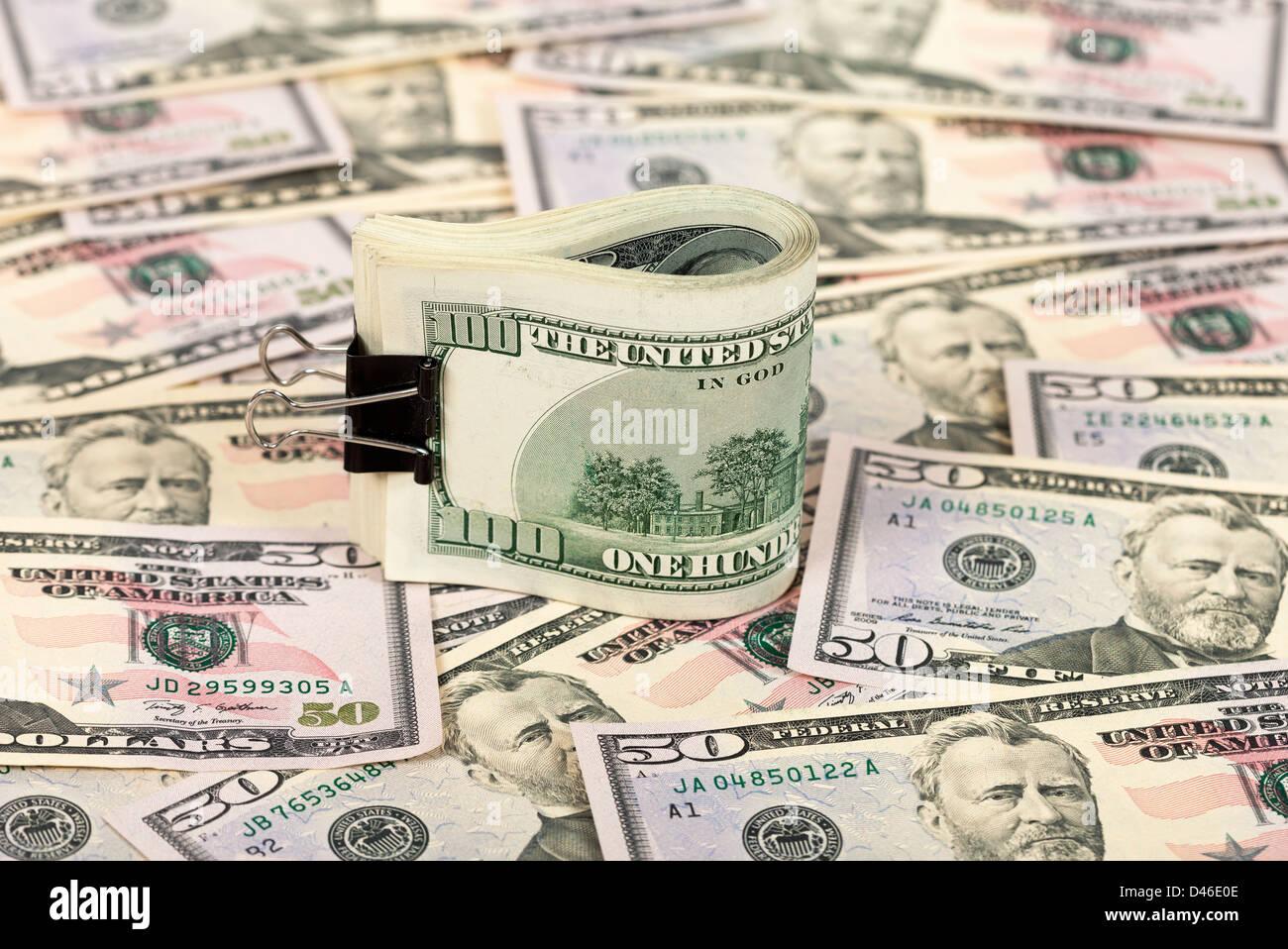 Folded hundred dollar bill on money background - Stock Image