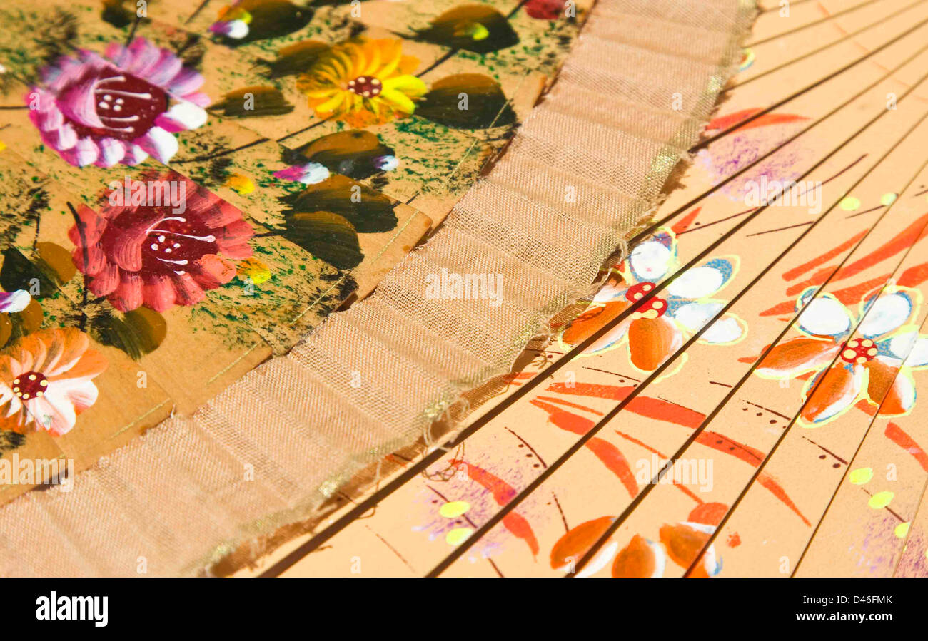 Two fans lying flat building a colorful flower-ornamented background. - Stock Image