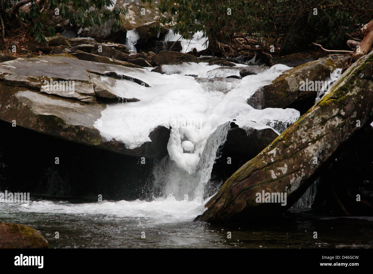 A winter abstract of ice formed on a rocky mountain creek. - Stock Image