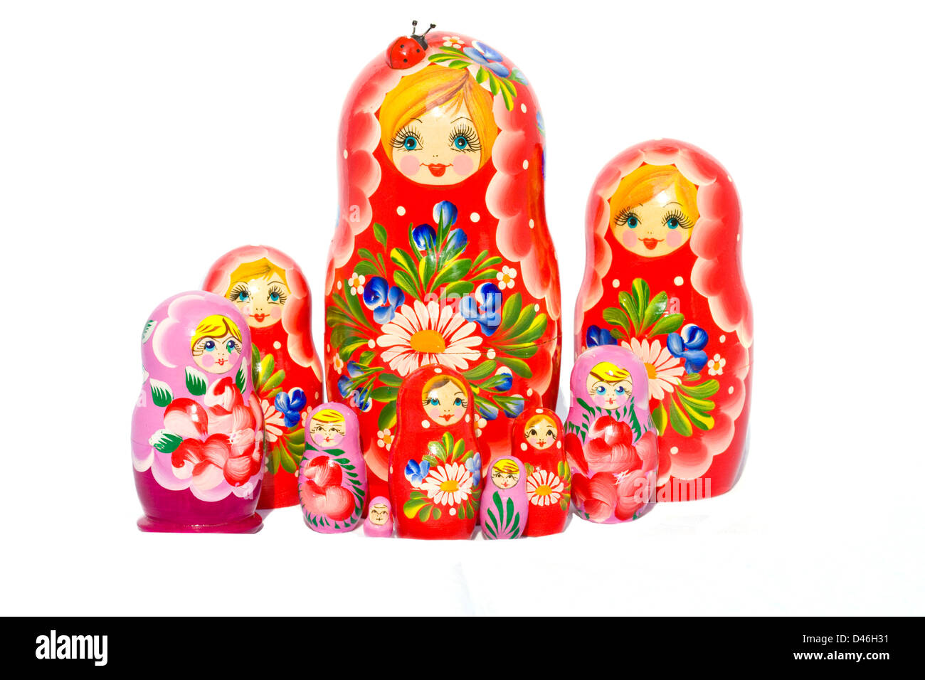 Red and violet Matryoshka doll families against white background. - Stock Image