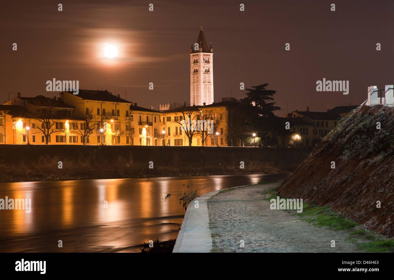 Verona - Adige river waterfronat and tower of San Zeno church at night - Stock Image