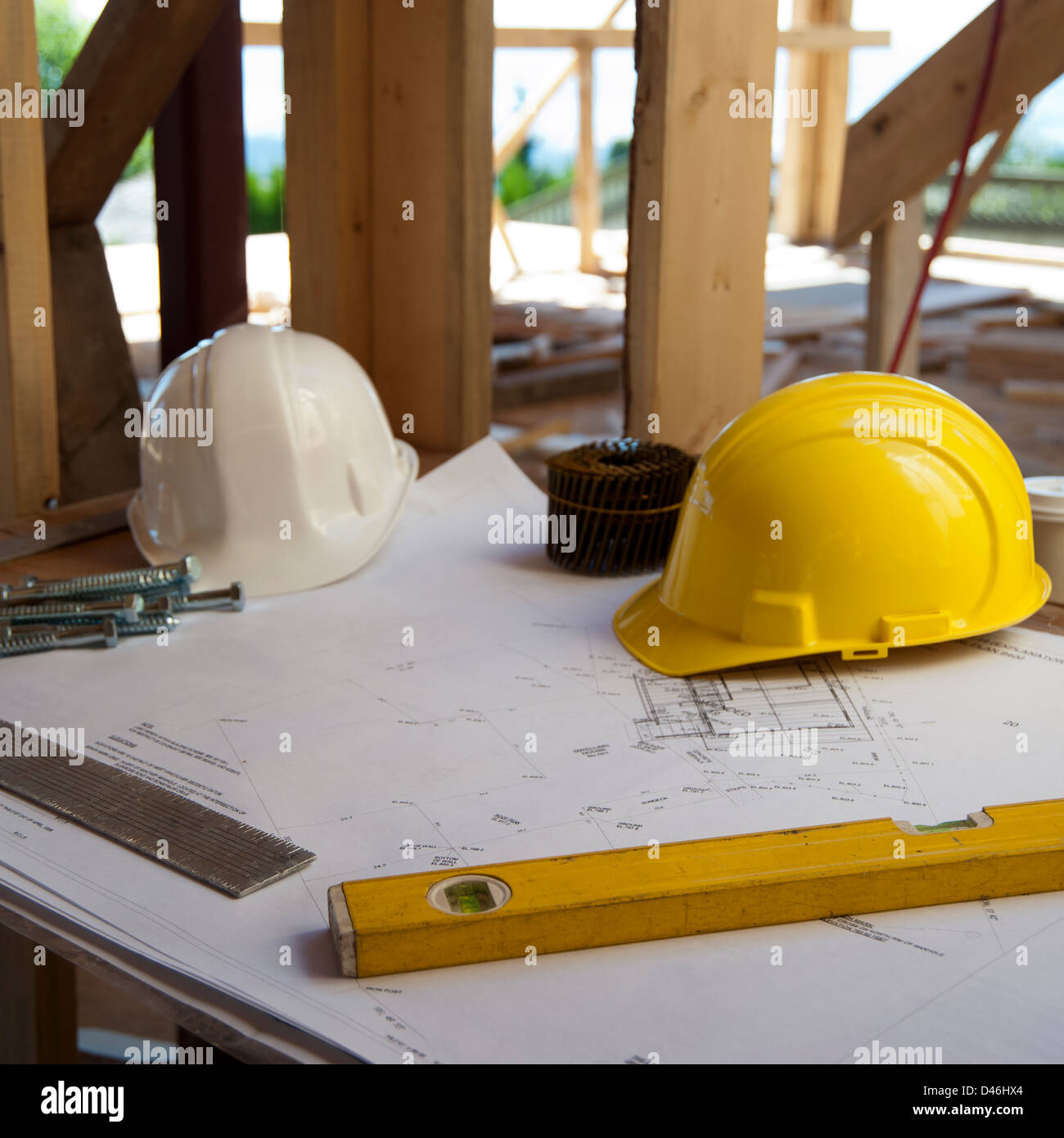 Hard hats, level tool and blueprints at construction site - Stock Image