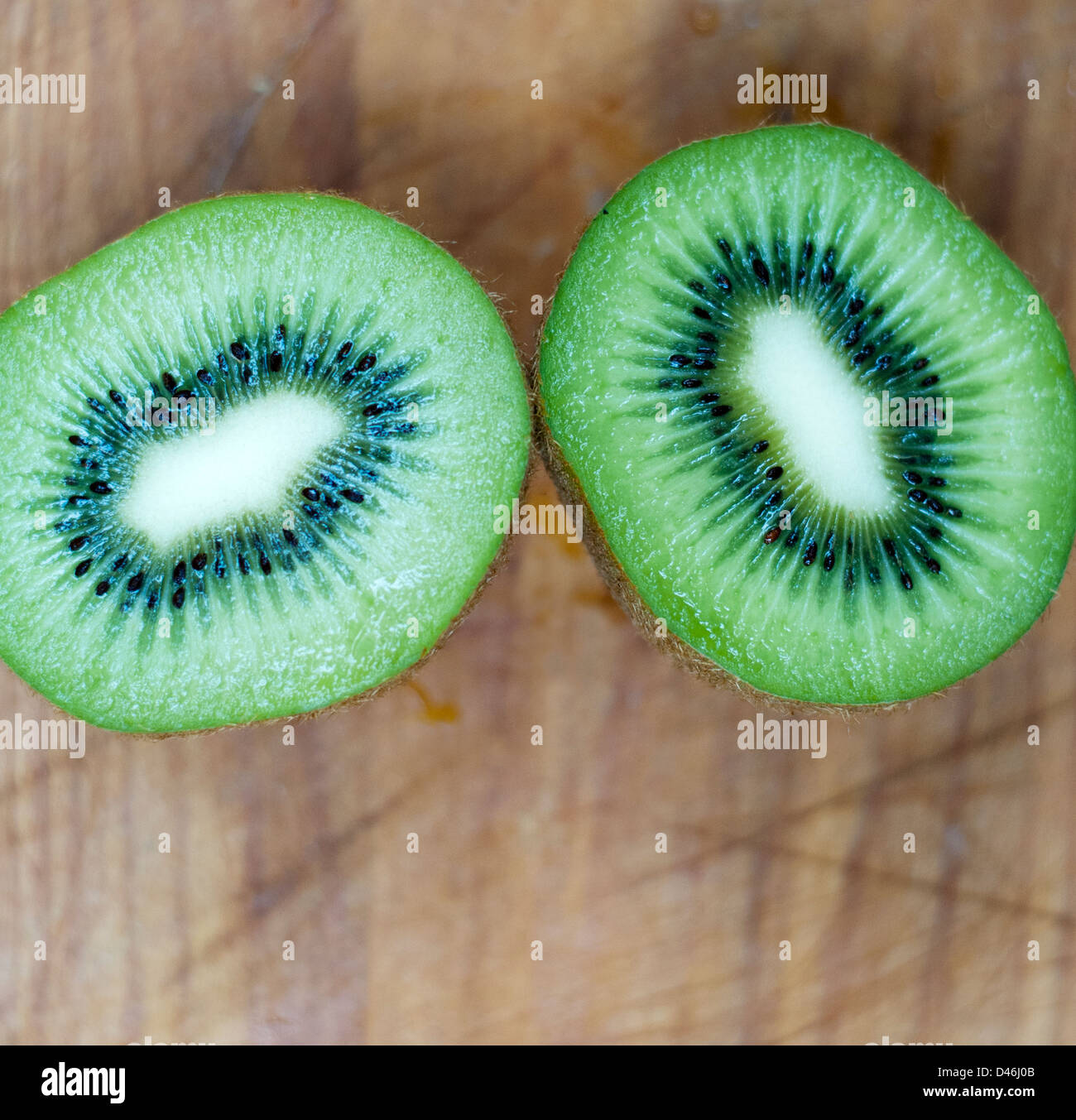 Kiwis sliced in half on old wooden scratched surface - Stock Image