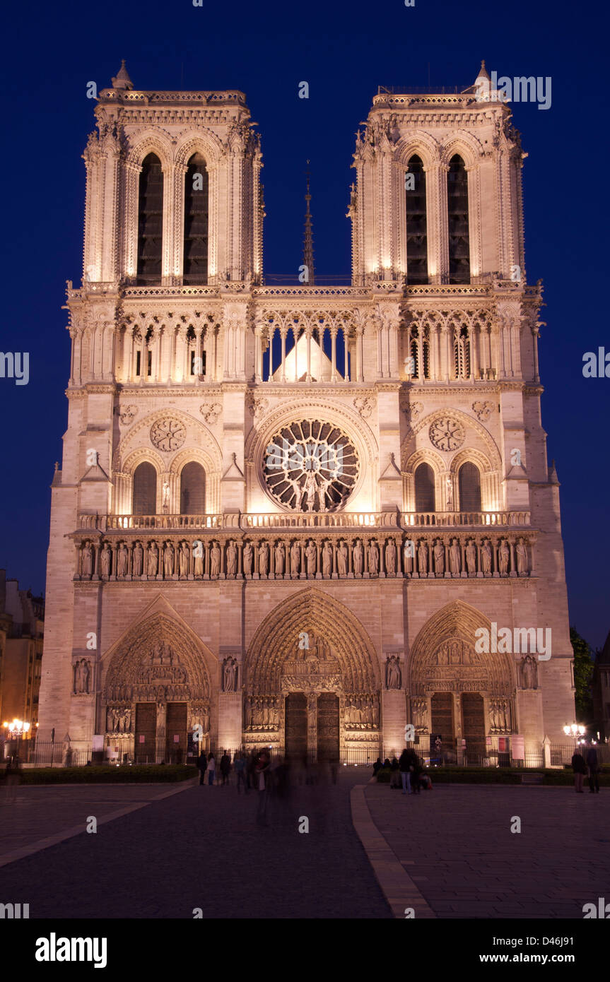 Iconic French architecture. The famous West Front of Notre Dame Cathedral, floodlit by night. A great Gothic masterpiece Stock Photo