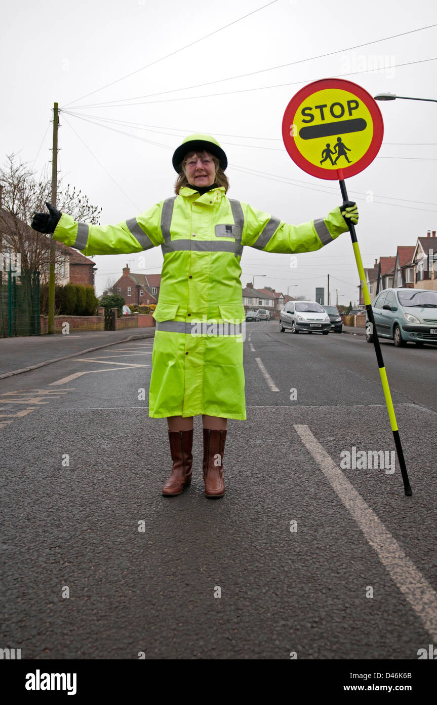 A British lollipop lady or crossing guard stopping traffic outside ...