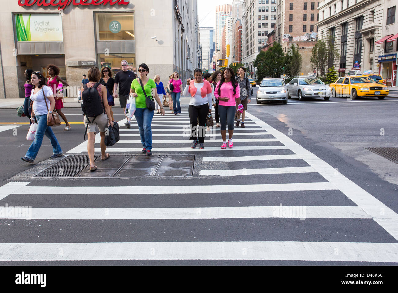 People crossing a street using a crosswalk in New York City - Stock Image