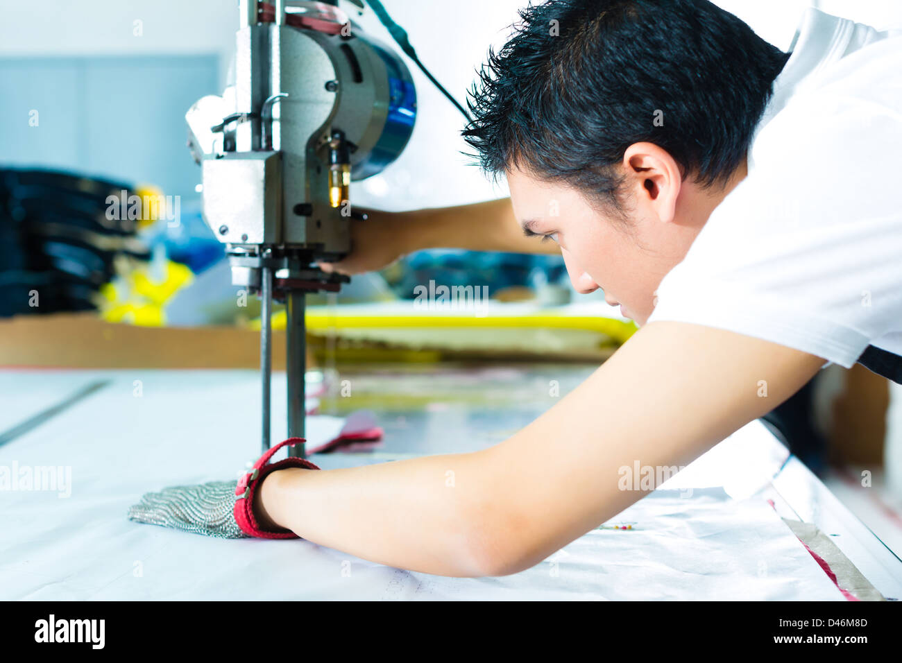 worker using a cutter - a large machine for cutting fabrics- in a Chinese textile factory, he wears a chain glove - Stock Image