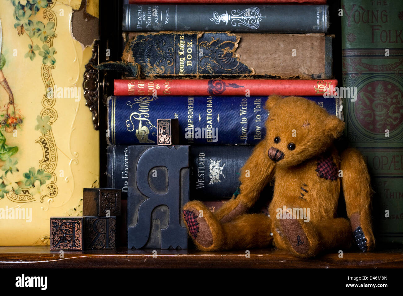 A Bookshelf Still Life Featuring Jointed Teddy Bear Antique Letter Press Letters Old Books And Victorian Photo Album