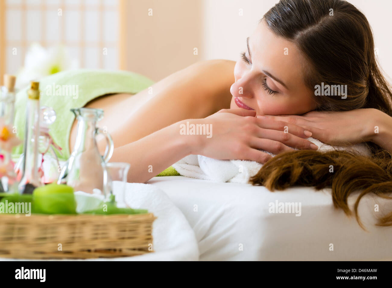 Beautiful Woman in relaxing in a spa situation, small bottles with essential oils standing beside her - Stock Image