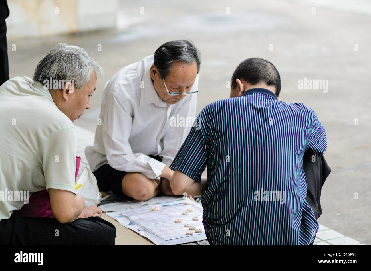 Elderly Chinese men playing an ancient form of Chinese chess, xiangqi, in a public park during their free time - Stock Image