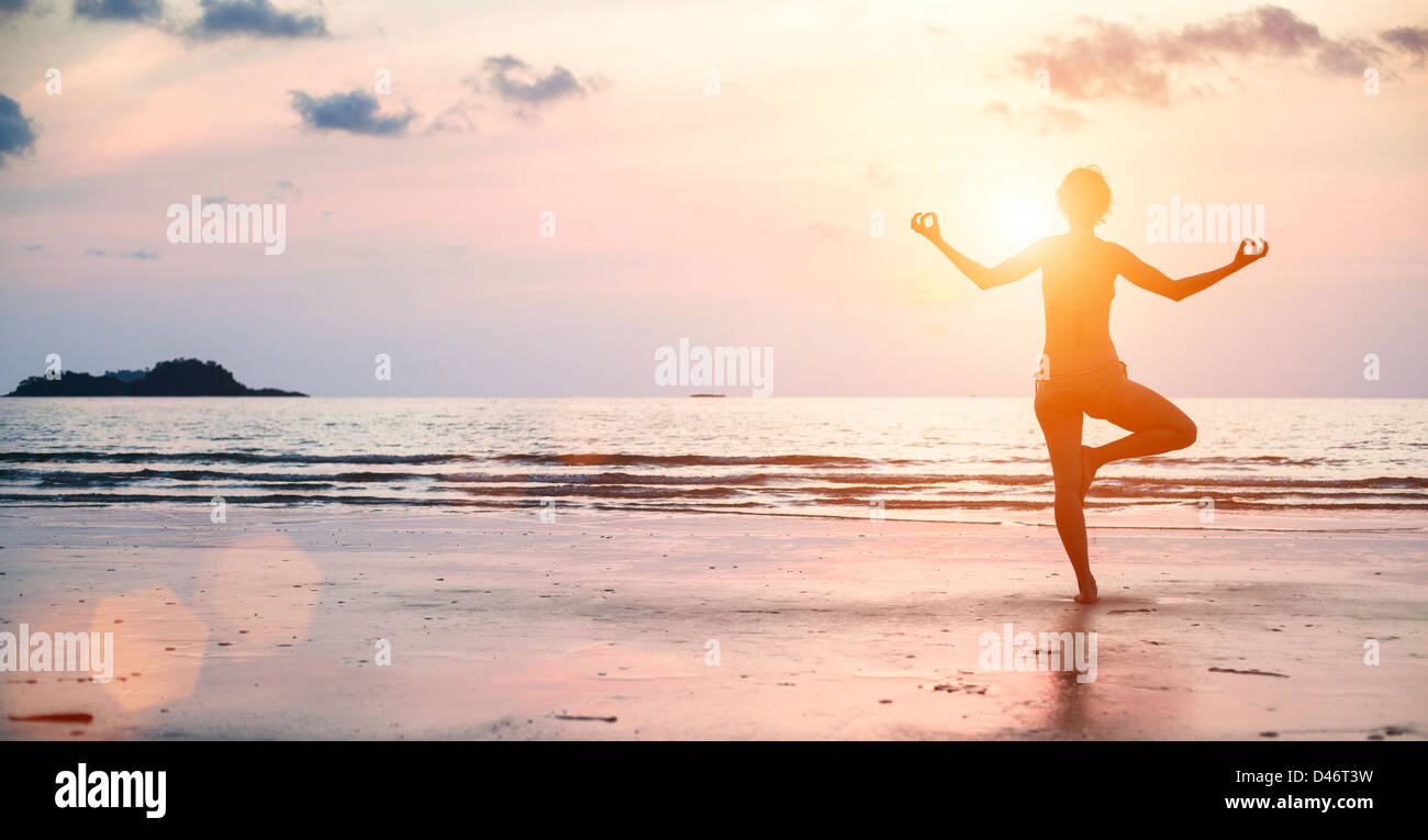 Yoga woman performs an exercise on the beach during sunset. - Stock Image