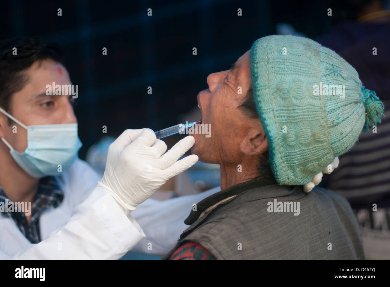 Dentist injecting man before tooth extraction - Stock Image