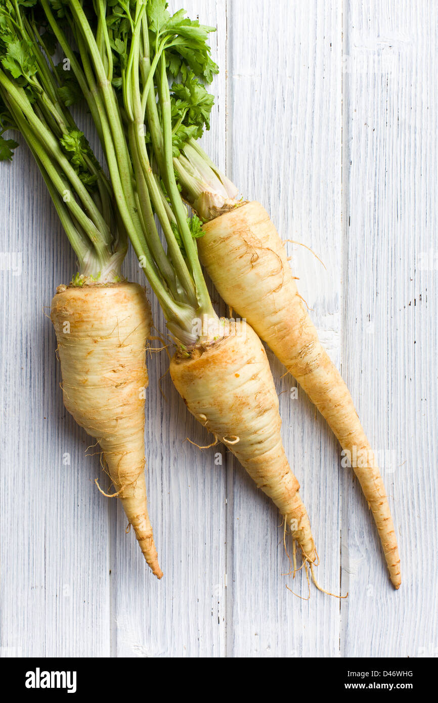 fresh parsnip on wooden table - Stock Image