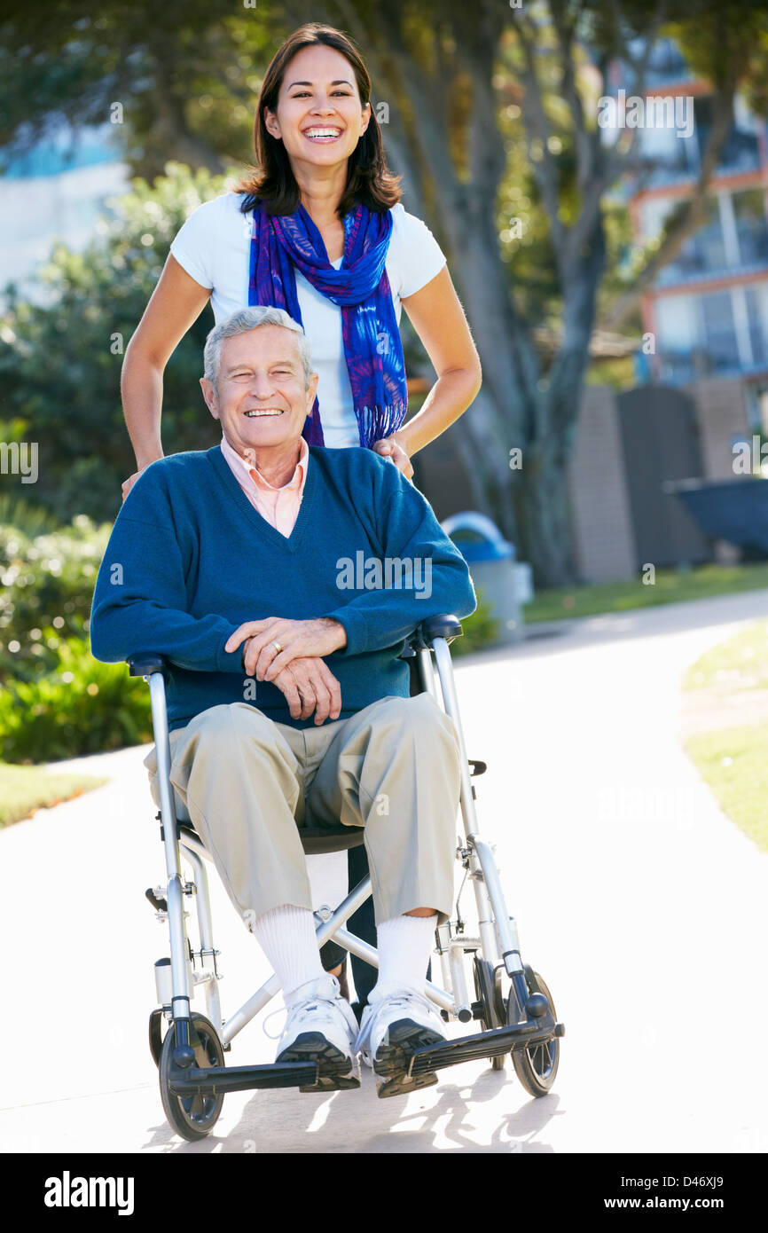 Adult Daughter Pushing Senior Father In Wheelchair - Stock Image