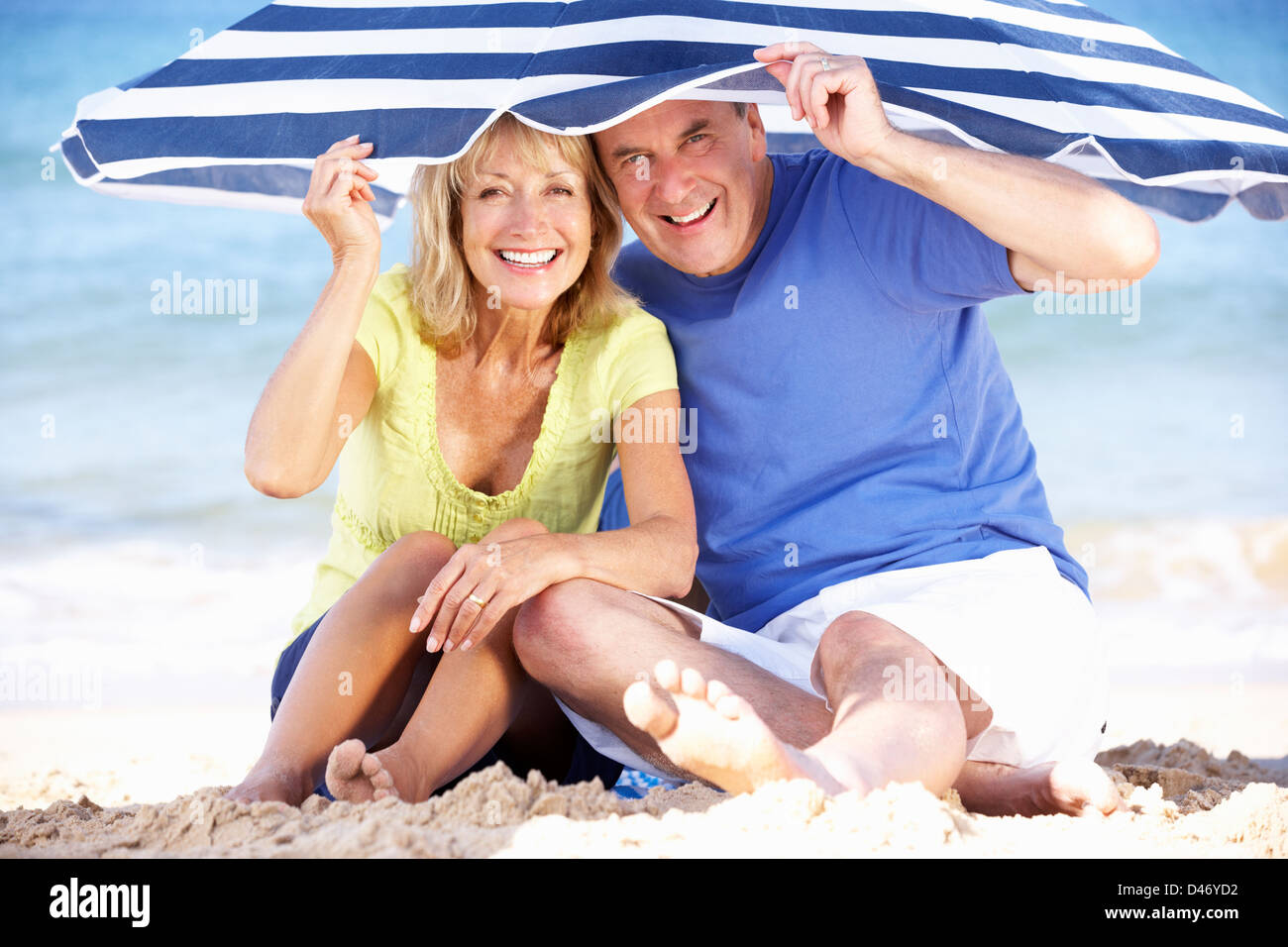 Senior Couple Sheltering From Sun Under Beach Umbrella - Stock Image