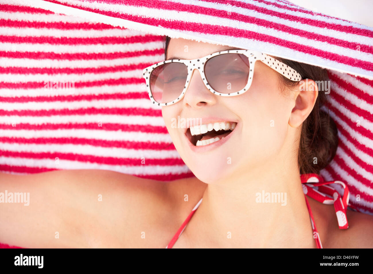 Woman Sheltering From Sun On Beach Holiday - Stock Image