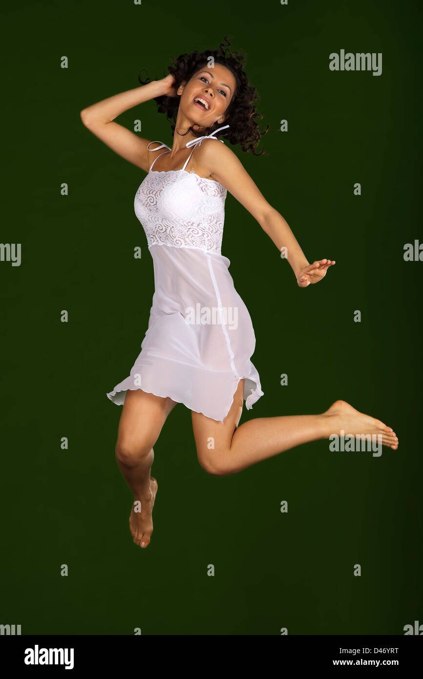 b129a66db9 beautiful young woman jumping on a green background with a white nightgown