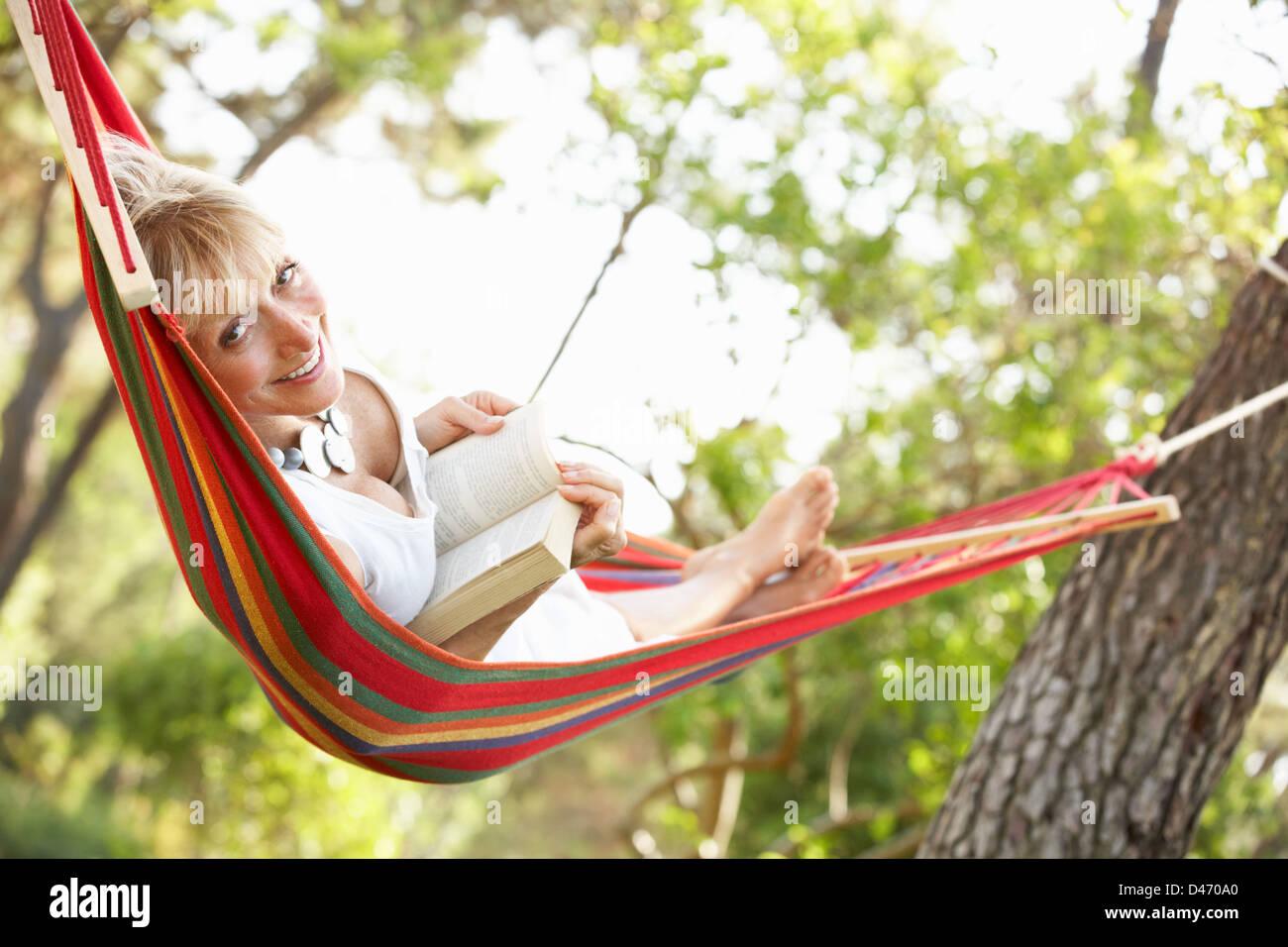 Senior Woman Relaxing In Hammock - Stock Image