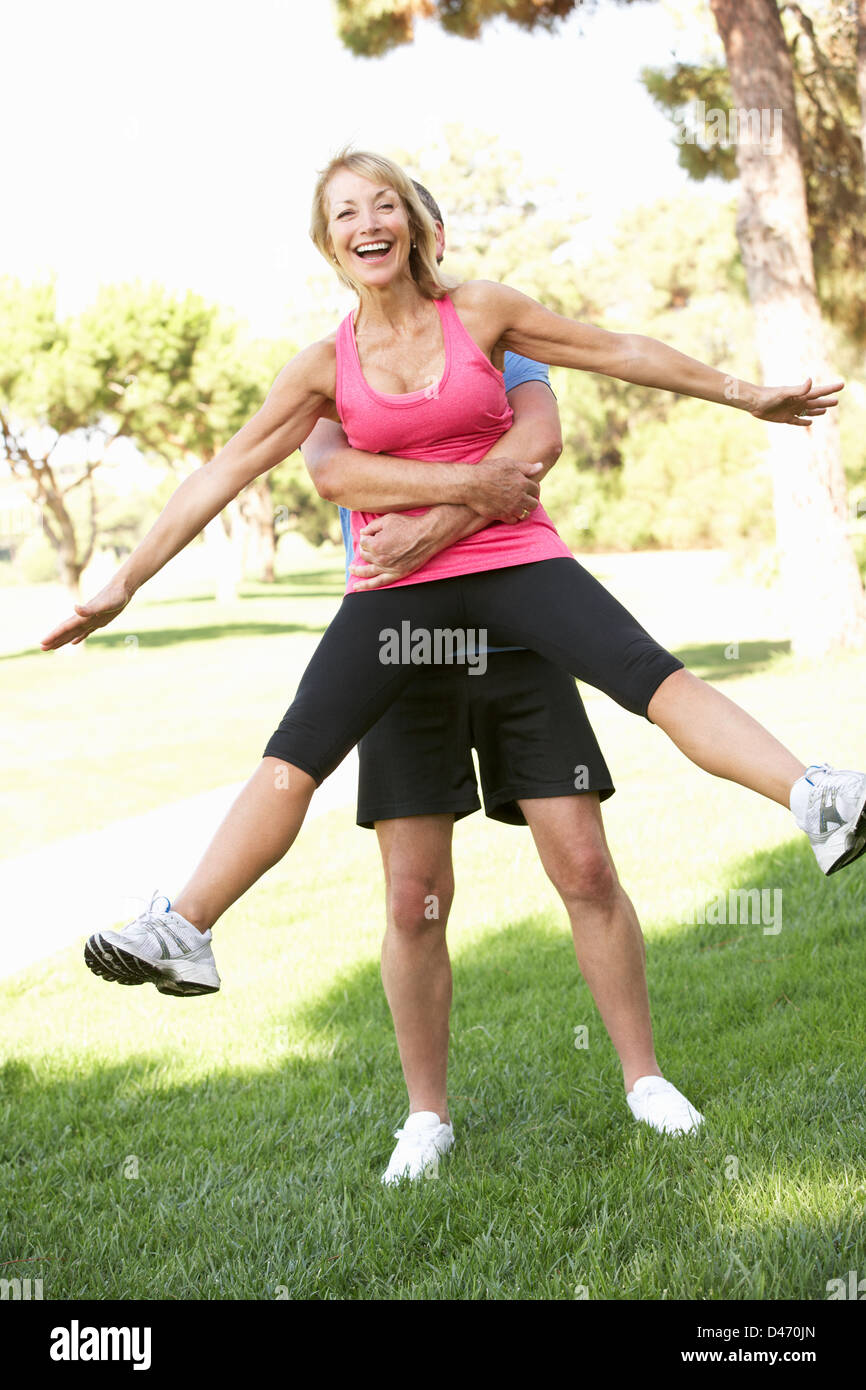 Senior Man Lifting Woman During excercise,fitness, In Park - Stock Image
