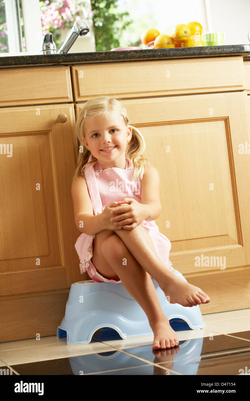 Girl Sitting On Plastic Step In Kitchen - Stock Image