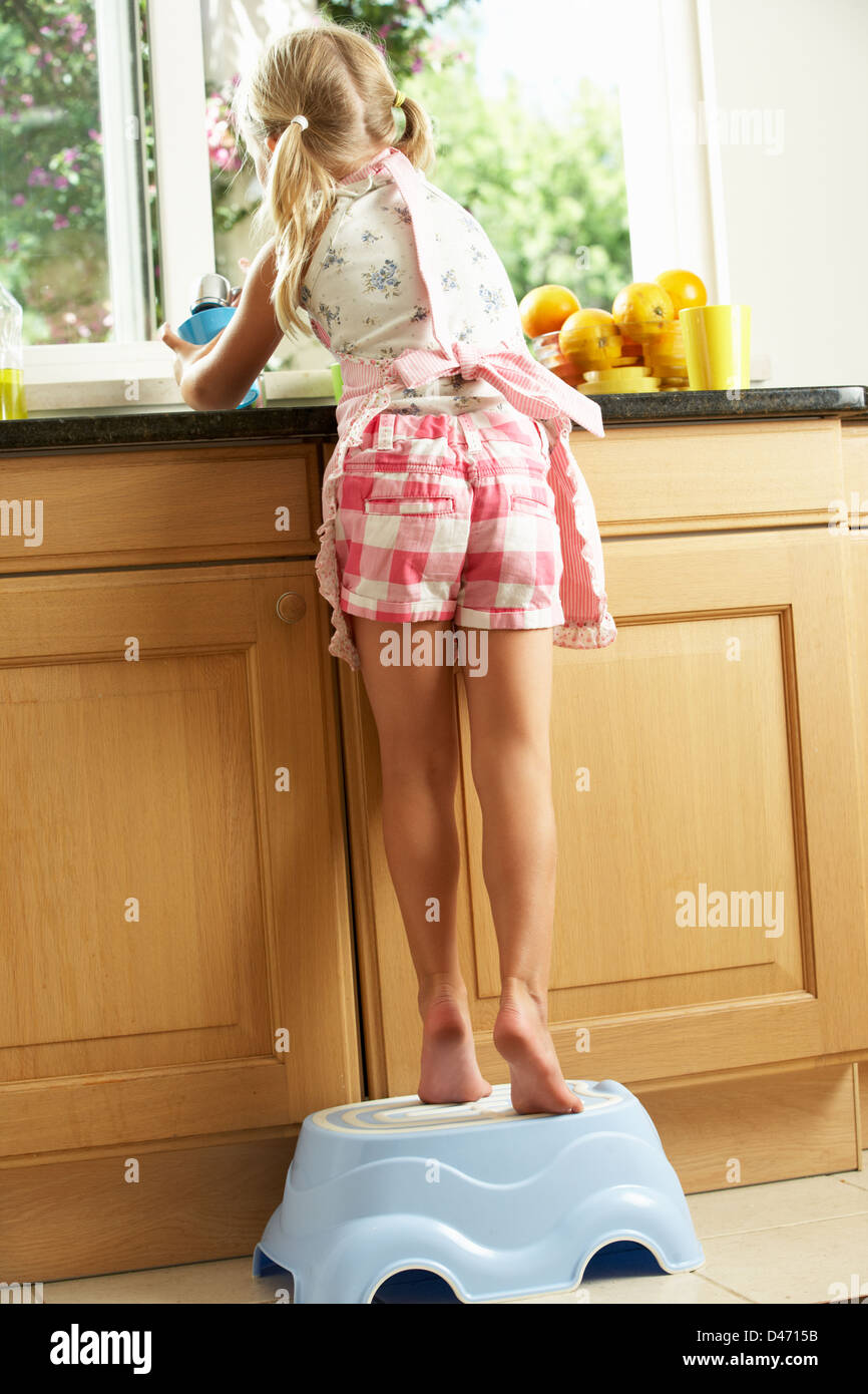 Girl Standing On Plastic Step In Kitchen Helping With Washing Up - Stock Image