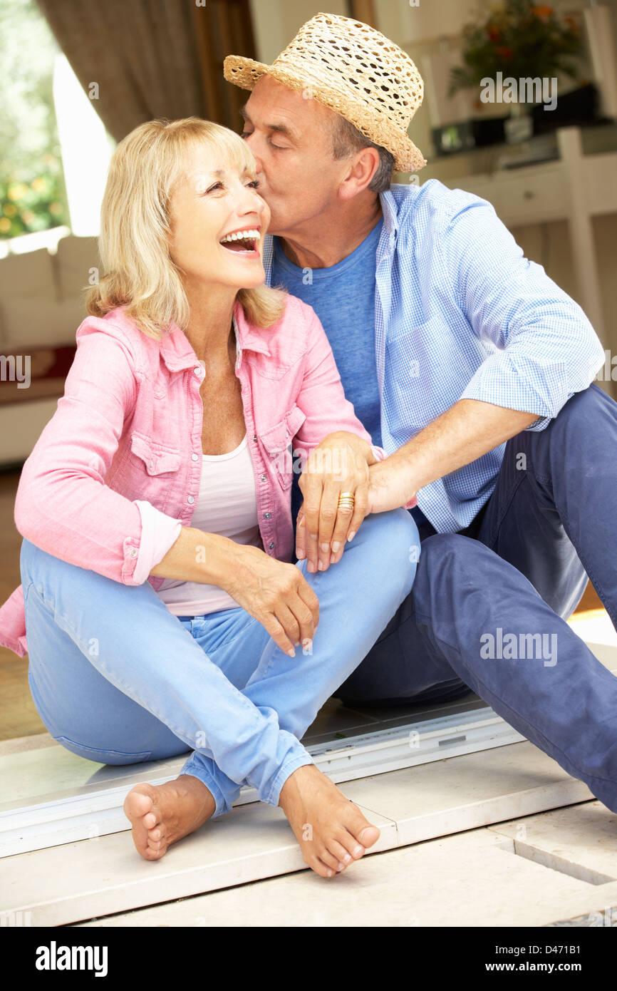 Senior Couple Sitting Outside House Stock Photo