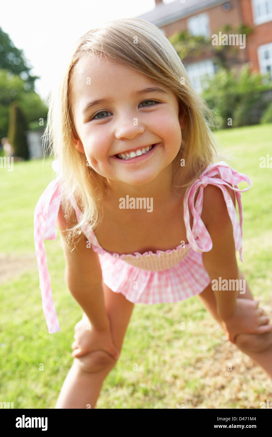 Portrait Of Young Girl Standing In Garden Wearing Swimming Costume - Stock Image