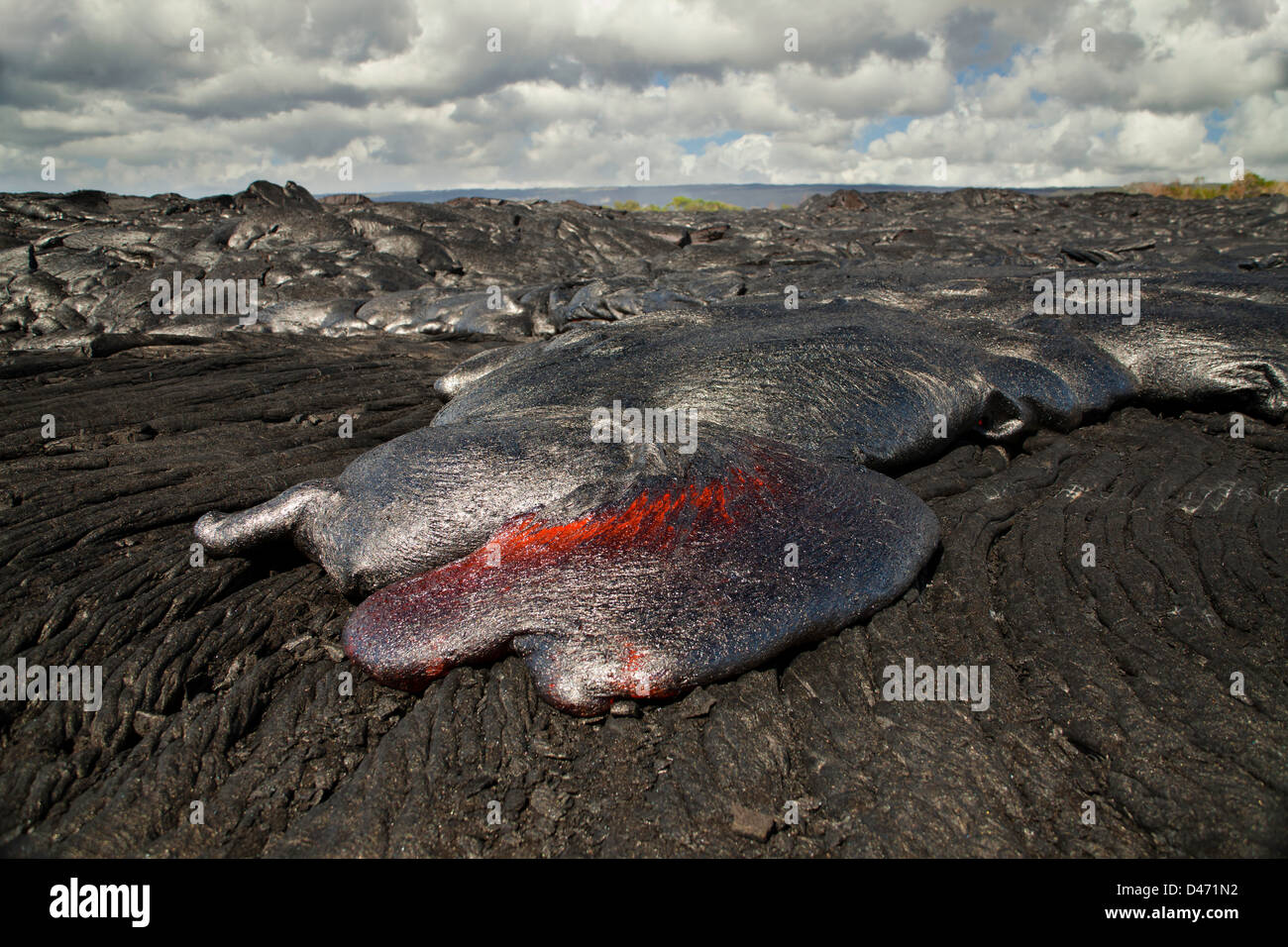 This new Pahoehoe lava flowing from Kilauea is covering an older Pahoehoe flow near Kalapana, Big Island, Hawaii. - Stock Image