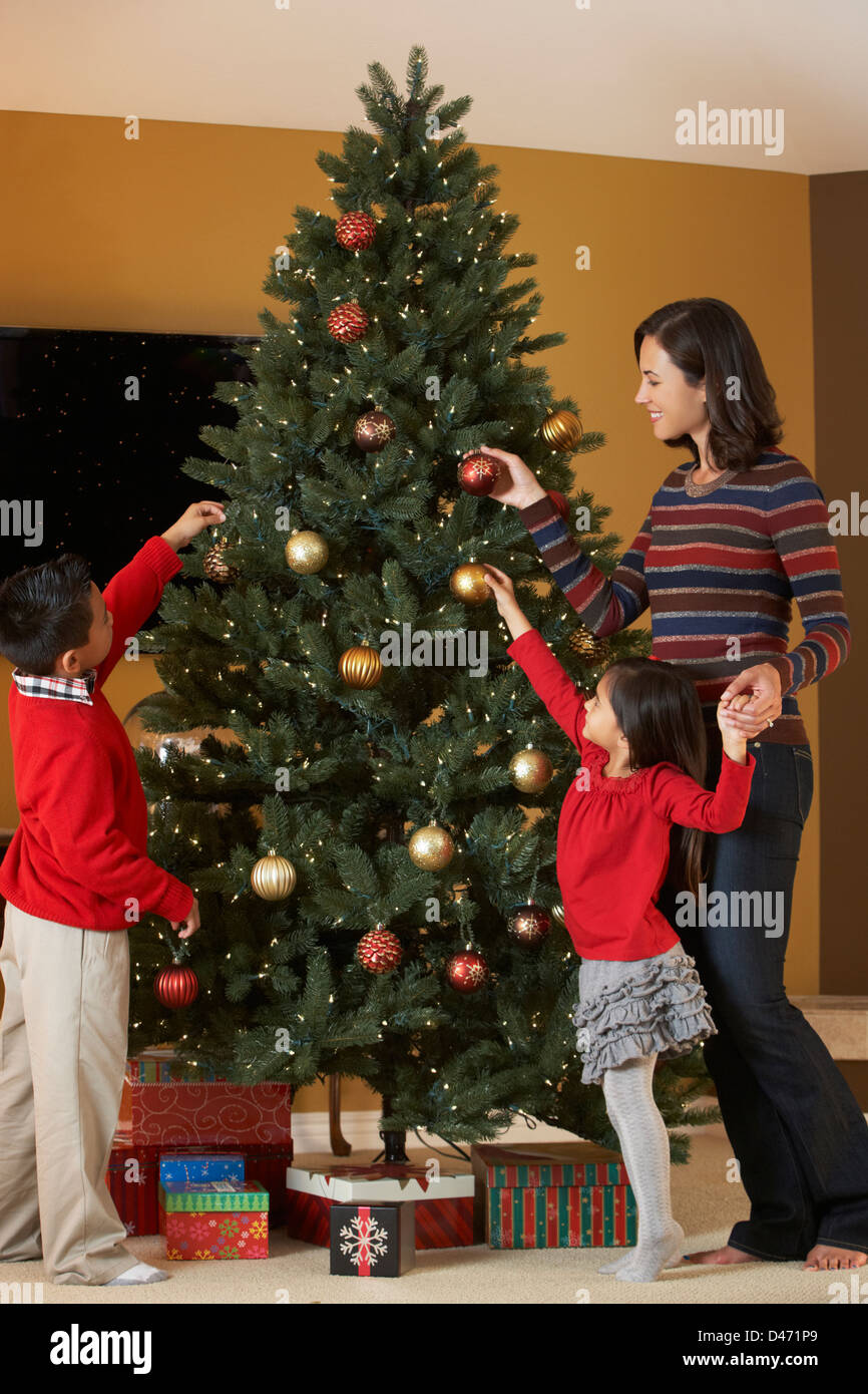 Mother And Children Decorating Christmas Tree Stock Photo