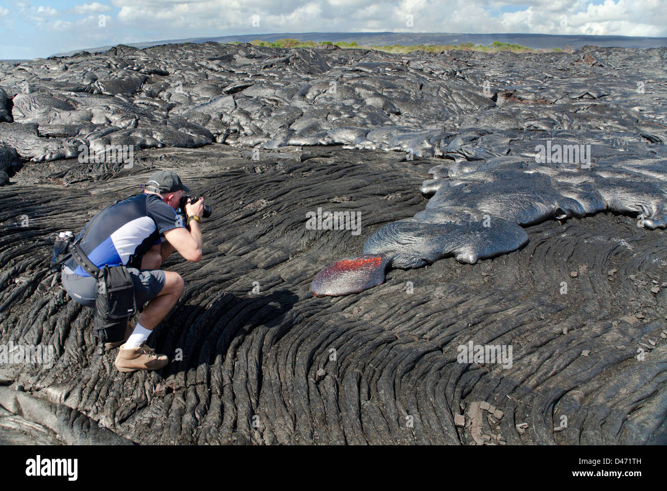 A photographer (MR) shooting a new, slow moving, Pahoehoe lava flow from Kilauea, Big Island, Hawaii. - Stock Image
